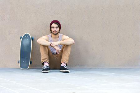 loitering: Handsome skateboarder haning around, sitting against a granite wall, with his skateboard next to him. Stock Photo