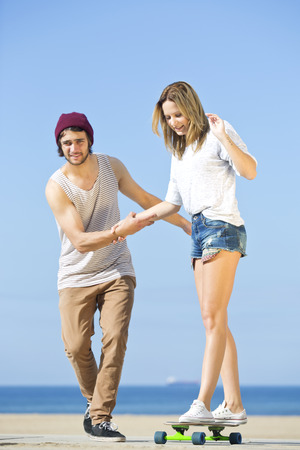 helps: Young woman, balancing on a skateboard, assisted by her boyfriend, who holds her, helps her, and pulls her along on a bright, sunny day at the beach.