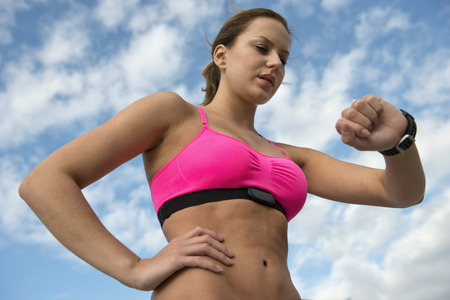 Fit, athletic woman wearing a sports bra and heart rate monitor checking her pulse during a training run Standard-Bild