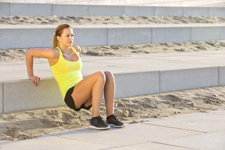 Joven, mujer atlética ejercitando su parte superior del cuerpo durante una sesión de entrenamiento bootcamp en un bulevar de playa