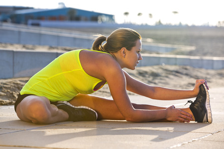hamstrings: Athletic woman stretching her hamstrings on a beach during a training run on a warm, summer evening.