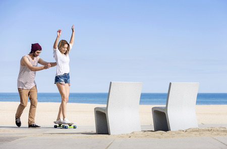 Couple, together on the boulevard of a beach, learning to skateboard on a summer day; young woman cheering whilst her man pushes her forward. photo