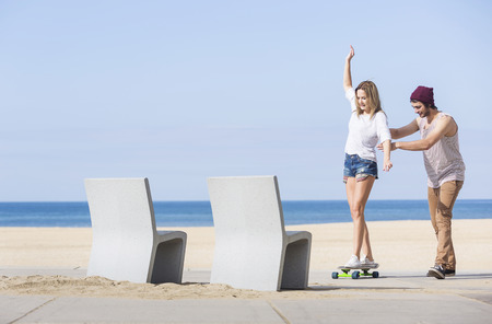 Girl balancing on a skateboard while a boy is teaching her on a boulevard with a beach and sea in the background photo