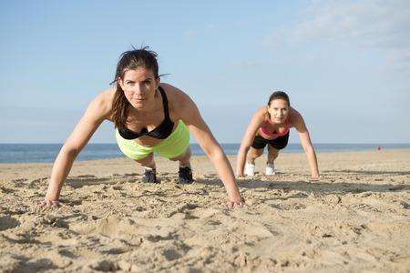 Two women doing pushups on a beach during an intense workout photo
