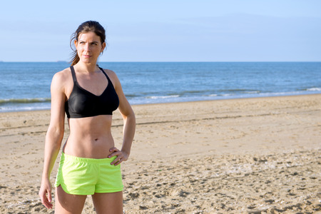 Strong, fit, sporty woman, wearing a sports bra and fluorescent shorts, standing on a beach during a short break of her training run, with her hand on her hip photo