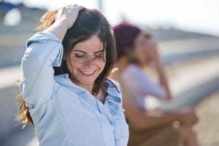 Portret van een introvert, zelfbewuste vrouw, op zoek naar beneden, en gaan met haar hand door haar haar.