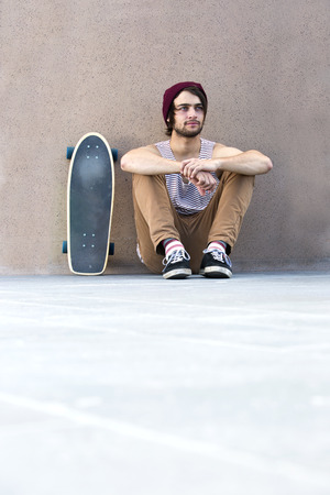 lost in thought: Skateboarder relaxes, lost in thought, sitting on a concrete floor against a granite wall, with his skateboard next to him