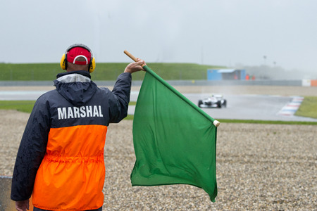 racing flag: Safety steward marshal waving a green flag at a race driver, indicating that the track ahead is clear, and the race condition is safe. All incidents are cleared Editorial
