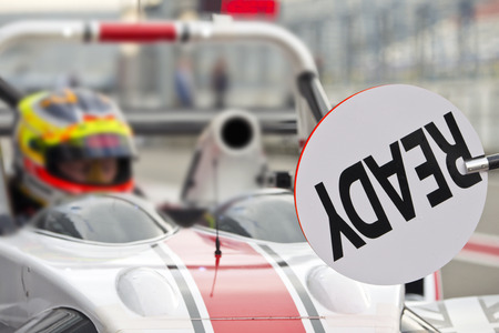 race car driver: lollipop sign, providing a race car driver with feedback during a pitstop