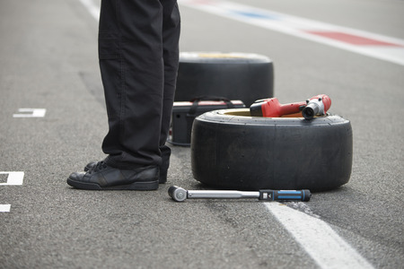 Pit crew mechanic waiting to get into achtion, with two replacement slick tires a power tool and a torque wrench lying on the asphalt of the pit lane behind him