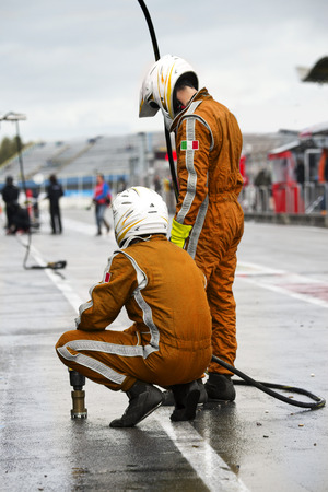anticipating: Pit Crew anticipating the arrival of their race car during a tyre change pitstop because of wet race conditions