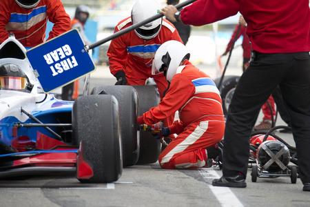 Teamwork en professionaliteit tijdens de behendige bandenwissel tijdens een autorace pitstop