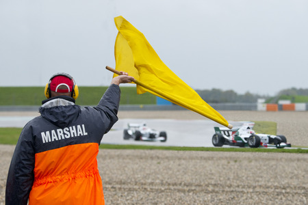 racing track: Safety Marshal waving a yellow flag as sign of caution for the race cars on a circuit.