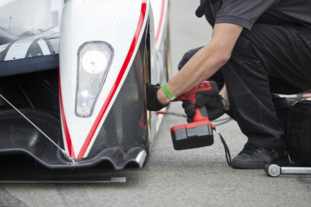 Pit crew changing the tires of a race car during a pitstop Stock Photo