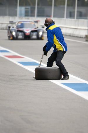 équipe de Pit, prêt et en attente pour une voiture de course approche dans la pitlane lors d'une course sur un circuit supercar