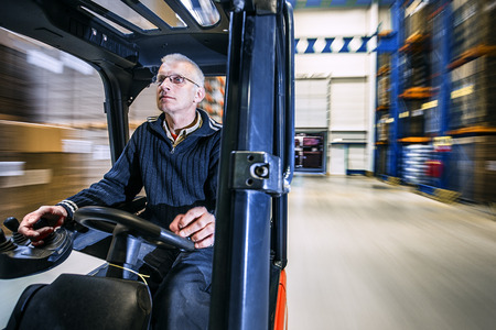 carretillas almacen: hombre que conduce una carretilla elevadora a través de un almacén en una fábrica