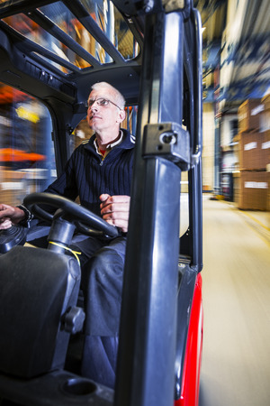 forklift driver: working in a warehouse on a forklift Stock Photo