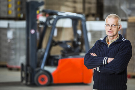proffesional: A warehouse employee is posing in front of his forklift, he is a proffesional forkliftdriver.