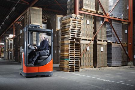 Reachtruck chauffeur in een pakhuis waar de pallets en karton worden opgeslagen Stockfoto