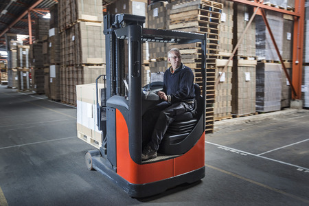 Fork lift operator drives through warehouse and is preparing the products for shipment Stock Photo