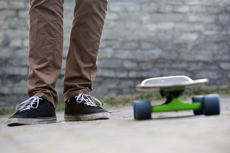 street wise: The two feet of a casually dressed man standing next to a skateboard in an urban setting, with a brick wall in the background. All earthy tones