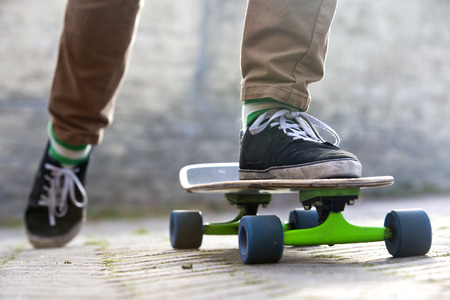 skateboard shoes: Skateboarder setting his board in motion by pushing off with one foot in an urban setting, representing the youth (sub) culture Stock Photo
