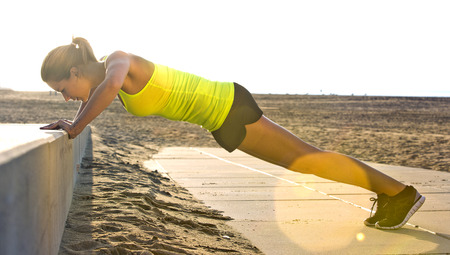 Young, pretty looking woman doing press ups on a concrete bench on the beach on a bright, slightly hazy, summer evening. Strong backlighting provides a warm feel Archivio Fotografico