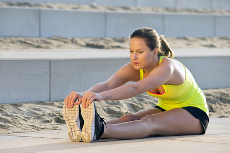 bending over: Young, pretty looking woman in sportswear, stretching and reaching her toes with her hand during an evening jog over the beach