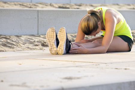 bending forward: Young, very flexible woman in sportswear, touching her knees with her nose. Shes stretching her muscles during a training run on the beach boulevard on a sunny summer evening.