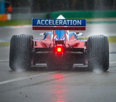 ASSEN, NETHERLANDS - OCTOBER 19, 2014: Formula A1 car with rain tires leaving a spray of water behind when leaving the pits lane during a wet race