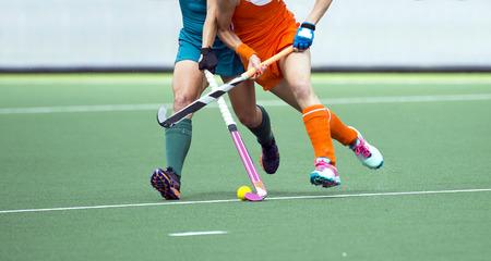 hockey cesped: Dos campo jugador de hockey, lucha por el balón en el centro del campo durante un intenso partido en césped artificial