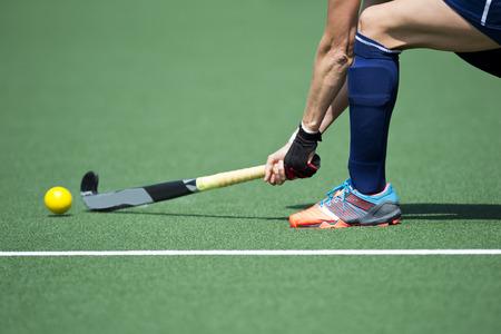 hockey sobre cesped: El campo jugador de hockey, que pasa con fuerza el bal�n a un compa�ero tream Foto de archivo