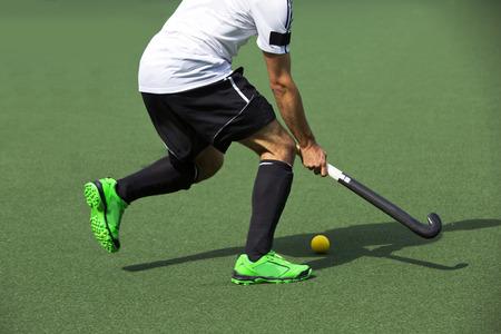 hockey cesped: El campo jugador de hockey, en la posesión de la pelota, corriendo sobre un terreno de juego, en busca de un compañero de equipo para pasar a Foto de archivo