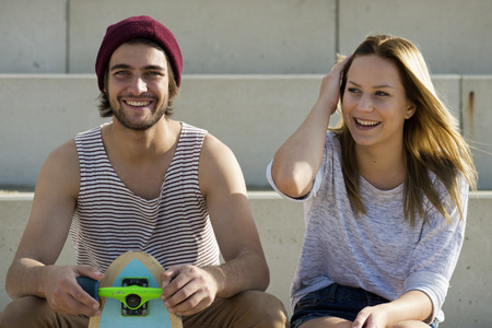 street wise: Portrait of a young, lovely, happy skateboarding couple on concrete steps on a bright, summer afternoon, with a pleasant, friendly atmosphere. Stock Photo