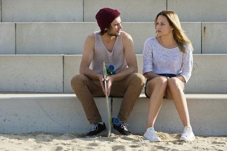 amigas conversando: pareja de jóvenes sentados en grandes medidas concretas, que participan en una conversación personal profunda