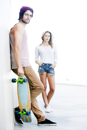 loitering: High Key image of a skateboarder couple as part of a subculture of youth lifestyles.