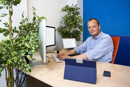 paperless: Manager, surrounded by various communication devices and computers, working in a paperless environment