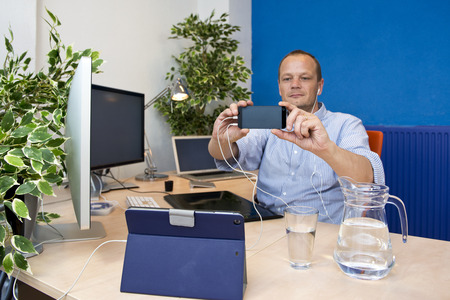 paperless: Man, in a paperless office, surrounded by all sorts of electronic devices, taking a selfie with his smart phone Stock Photo