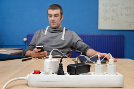 plugged in': Power strip with various plugs, adapters and chargers plugged in to charge a number of different electronic devices, with a man texting on his cell phone in the background Stock Photo