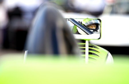 race car driver: The nervous, tencely concentrated look in the eyes of a race car driver in his car on the starting grid of a race track, reflected in the side mirror of his vehicle.