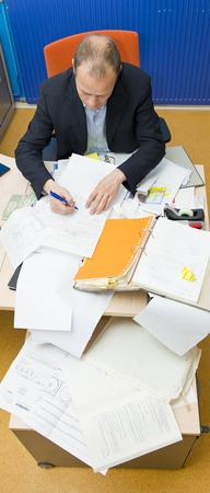 Manager taking notes in a messy office, cluttered with paperwork and office supplies, seen from above photo