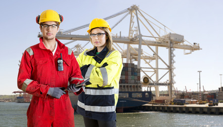 safety gear: Two dockers, wearing safety gear, protection and work clothing, posing in front of a large container ship in an industrial harbor