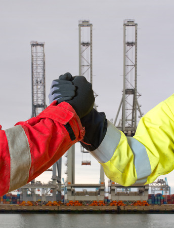 lucrative: Handshake between two people in work clothing, symbolizing a lucrative deal for in- or export against three harbor cranes Stock Photo