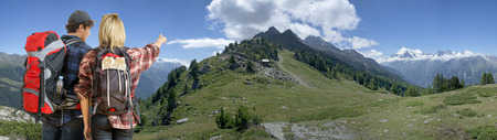 anticipating: A couple hiking in an  Alpine Mountain range, along a ridge, anticipating the slopes and weather changes