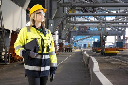 Docker Femme et le port de chargement inspectorontinuous et déchargement des conteneurs de fret maritime au port de Rotterdam, à l'aide d'énormes grues et chariots automatisés Banque d'images