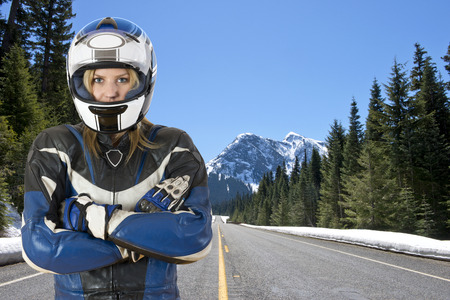 Portret van een vrouw fietser kuiken, het dragen van een motorrijder pak en helm, die zich voordeed op een besneeuwde weg in mooie berg scenics, omgeven door grote pijnbomen en de smeltende sneeuw in de warme lentezon Stockfoto
