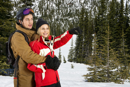 wintersports: Young couple, enjoying the scenery in a snowy landscape with pine trees during the wintersport