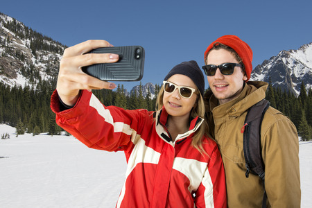 wintersport: Young couple taking a selfie in front of a beautiful winter landscape during their wintersport Stock Photo