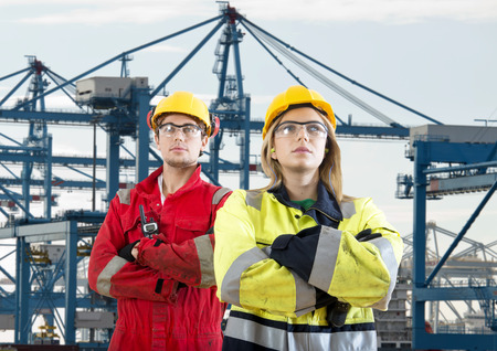 self assured: Two tough looking dockers in safety clothing posing in front of a huge container terminal Stock Photo