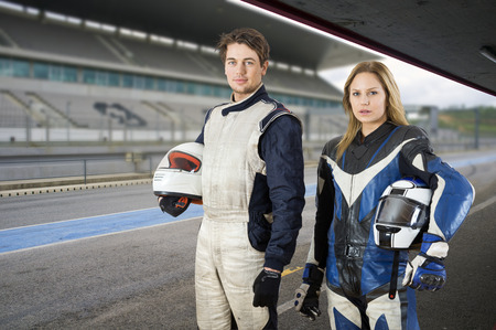 Motor cyclist and a race car driver posing in the pit box in front of the grand stand of a race track